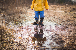 Low section of boy standing in dirty puddleの写真素材 [FYI03697244]