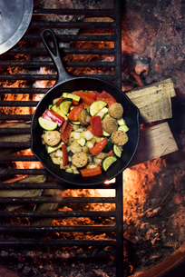 Overhead view of food cooking in pan over fire pitの写真素材 [FYI03697304]