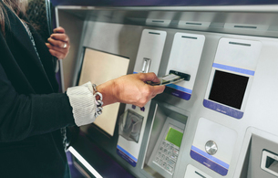 Midsection of woman inserting card in ATM machineの写真素材 [FYI03697407]