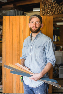 Portrait of man holding planks while standing against wood in workshopの写真素材 [FYI03697603]