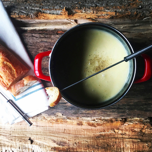 Overhead view of bread with cheese fondue on wooden tableの写真素材 [FYI03698278]