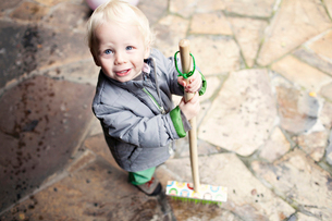 High angle view of boy holding broom while standing in porchの写真素材 [FYI03698306]