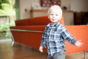 Portrait of cute boy standing against sofa at homeの写真素材 [FYI03698312]