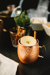 Close-up of drink garnished with apple slice and cinnamonの写真素材 [FYI03698672]