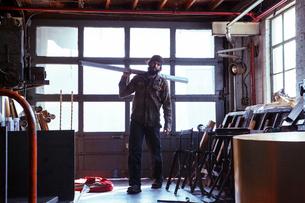Portrait of worker carrying metal planks in workshopの写真素材 [FYI03699079]