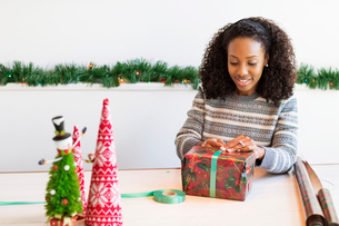 Woman wrapping Christmas present while sitting at tableの写真素材 [FYI03699088]