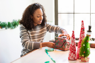 Woman wrapping Christmas present while sitting at homeの写真素材 [FYI03699089]