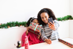 Happy mother and daughter taking selfie with Christmas present at homeの写真素材 [FYI03699102]