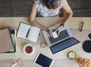 Overhead view of businesswoman using smart phone while sitting at table in home officeの写真素材 [FYI03699514]