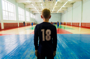 Rear view of player standing at indoor soccer courtの写真素材 [FYI03699655]