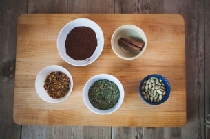 High angle view of various spices in bowls on cutting board over wooden tableの写真素材 [FYI03699754]
