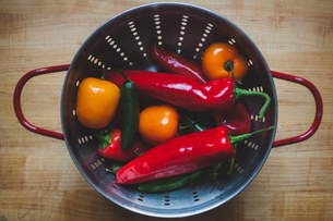 Overhead view of chili peppers and tomatoes in colander on wooden tableの写真素材 [FYI03699791]