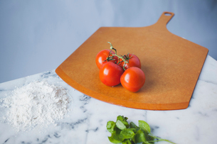 High angle view of cherry tomatoes with flour and mint leaves on marbleの写真素材 [FYI03699811]
