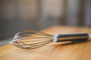 Close-up of wire whisk on wooden tableの写真素材 [FYI03699813]