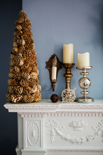 Christmas decoration and candles on mantelpieceの写真素材 [FYI03700154]