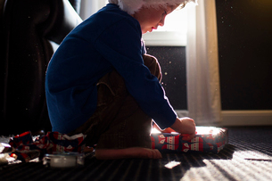 Boy in warm clothing wrapping present while crouching on carpet at homeの写真素材 [FYI03700601]