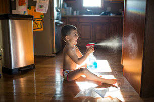 Side view of boy spraying water on wooden cupboard while sitting on floor at homeの写真素材 [FYI03700822]