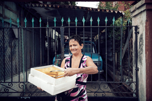 Portrait of woman selling food while standing against gateの写真素材 [FYI03701432]