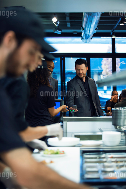Businessman paying bill through smart phone while standing in restaurantの写真素材 [FYI03701542]