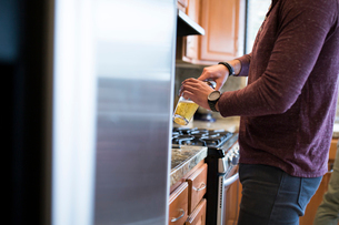 Midsection of man pouring beer in glass while standing in kitchenの写真素材 [FYI03701774]