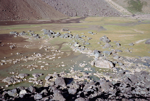 Rocks in dirty lake by mountainの写真素材 [FYI03701848]
