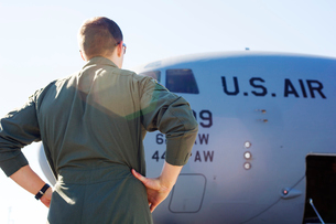Low angle view of army soldier standing by military airplane on runwayの写真素材 [FYI03701959]