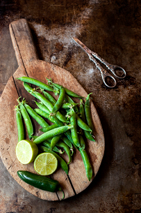 High angle view of green peas with lemon and chili pepper on cutting board by scissors at old counteの写真素材 [FYI03703116]