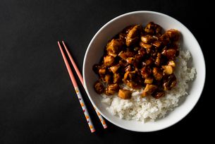 Overhead view of rice and chicken served in bowl with chopsticks on tableの写真素材 [FYI03703197]