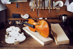 Incomplete violin and planks on workbench in workshopの写真素材 [FYI03703275]