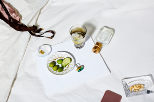 High angle view of food and drink with personal accessories on bedの写真素材 [FYI03703385]