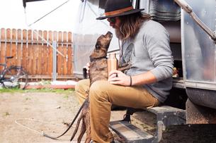Man looking at dog while sitting on steps of camper vanの写真素材 [FYI03703416]