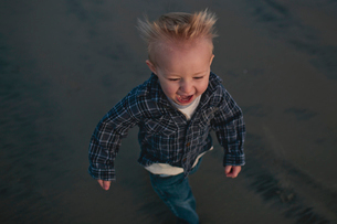 High angle view of cheerful boy walking on sand at beachの写真素材 [FYI03703580]