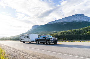 Pick-up truck with motor home on road against mountainsの写真素材 [FYI03703723]