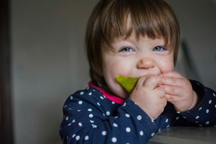 Close-up portrait of girl eating fruit at homeの写真素材 [FYI03703921]