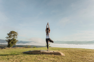 Rear view of woman doing yoga on grassy field against skyの写真素材 [FYI03704000]