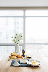 Food and drinks with flower vase arranged on dining table by window at homeの写真素材 [FYI03704486]