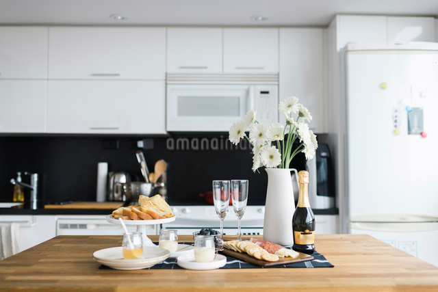 Food and drinks with flower vase arranged on table in kitchenの写真素材 [FYI03704492]