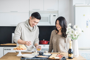 Woman looking at boyfriend preparing breakfast in kitchenの写真素材 [FYI03704498]