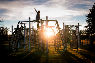 Girl playing on metallic structure at park against cloudy skyの写真素材 [FYI03704727]