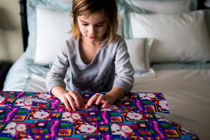 Girl wrapping gift box while sitting on bedの写真素材 [FYI03704758]