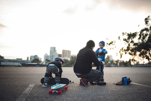 Father assisting sons in preparation for skateboarding at fieldの写真素材 [FYI03704789]