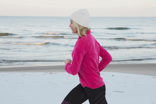 Side view of teenage girl jogging at beach against seaの写真素材 [FYI03705196]