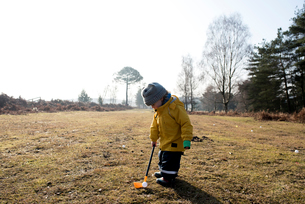 Girl playing miniature golf on field against skyの写真素材 [FYI03705218]