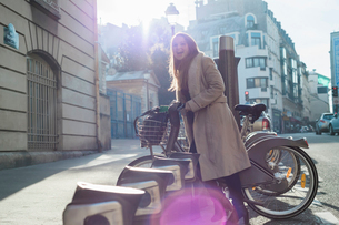 Cheerful woman removing bicycle form rack at city streetの写真素材 [FYI03705237]