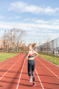 Portrait of athlete running on sports track against skyの写真素材 [FYI03705412]