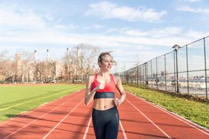 Female athlete running on sports track against skyの写真素材 [FYI03705417]