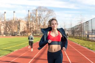Female athlete running on sports track against skyの写真素材 [FYI03705418]