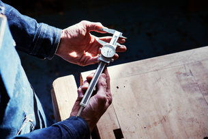 Midsection of carpenter holding vernier caliper at table in workshopの写真素材 [FYI03705475]