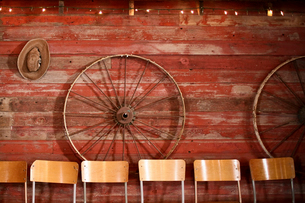 Chairs against wheels hanging on wooden wallの写真素材 [FYI03705657]