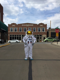 Person wearing astronaut costume standing on city street against cloudy skyの写真素材 [FYI03705765]